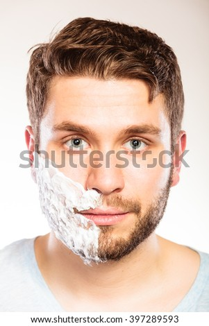 Young man with shaving cream foam on half of face beard. Handsome guy preparing to shave. Skin care and hygiene. - stock photo