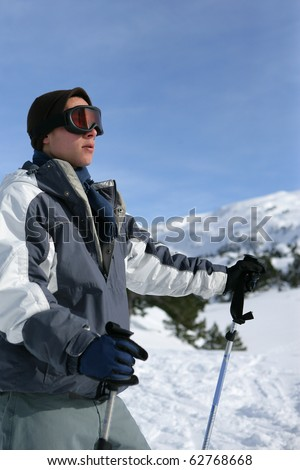 Young man with skis in snowy landscape - stock photo