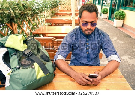Young man with smartphone sitting on cafe table outside - Refugee with facial serious expression using mobile technology - Traveler guy wifi connected writing messages - Concept of communication   - stock photo