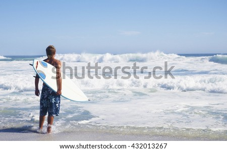 young man with surf board on beach in summer vacation day - stock photo