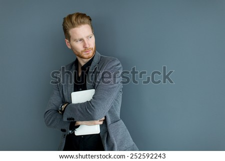 Young man with tablet by the wall - stock photo