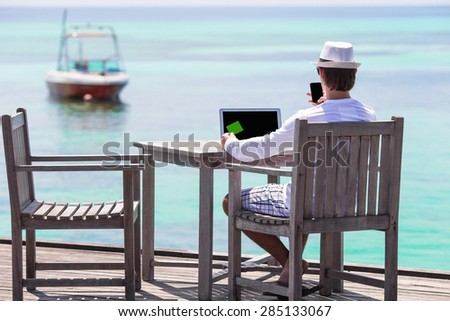 Young man with tablet computer on tropical beach - stock photo