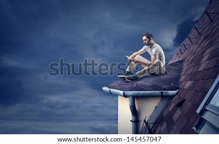 young man with tablet sitting on the roof in the night - stock photo