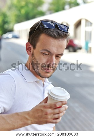 young man with take away coffee cup, selective focus - stock photo