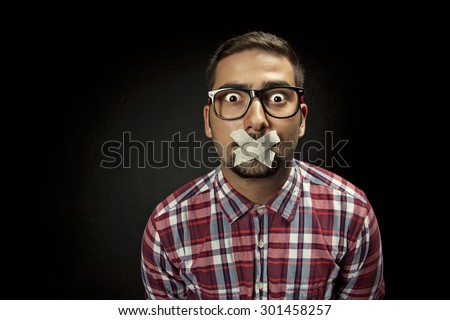 Young man with taped mouth - stock photo