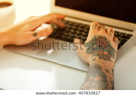 Young man with tattoo using laptop at the table at home - stock photo