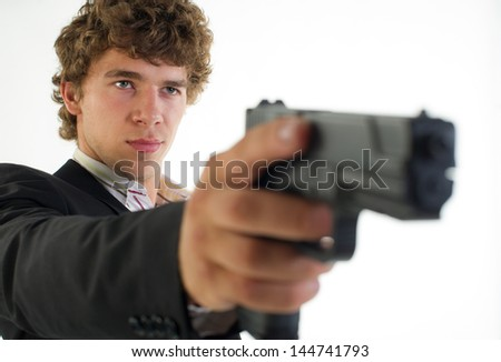 young man with the gun in a hand aims aside on a light background - stock photo