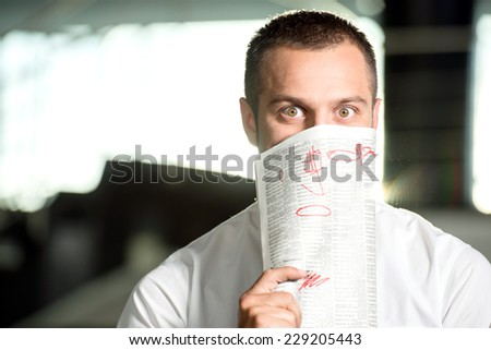 Young man with the newspaper, he is looking for a job. - stock photo
