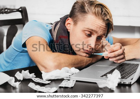 Young man with thermometer sick blowing his nose in his living room working notebook  - stock photo