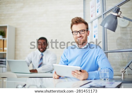 Young man with touchpad looking at camera during work in office - stock photo