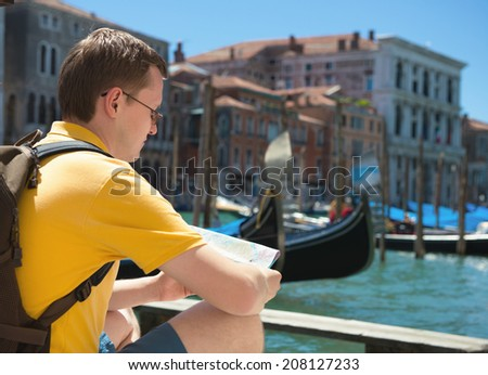 Young man with tourist map in Venice - stock photo