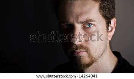 Young man with upset and serious expression - stock photo