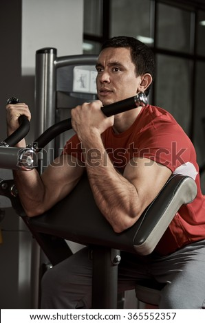 Young man with weight training equipment working out arm muscles in sport club. Strength, endurance and determination concept.   - stock photo