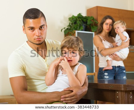 Young man with wife and two children having quarrel in home interior - stock photo