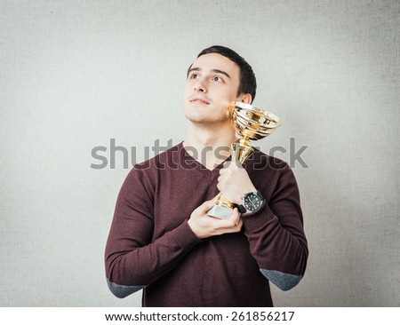 young man won and holds the cup in his hands - stock photo
