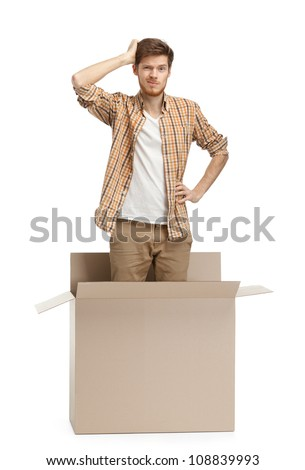 Young man wonders why he is inside the box, isolated, white background - stock photo