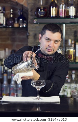 young man working as a bartender in a nightclub bar - stock photo