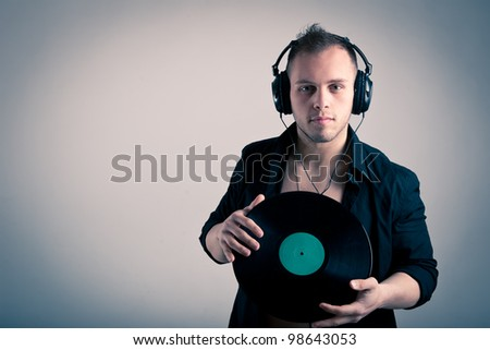 Young man working as dj with ear-phones and disc. - stock photo