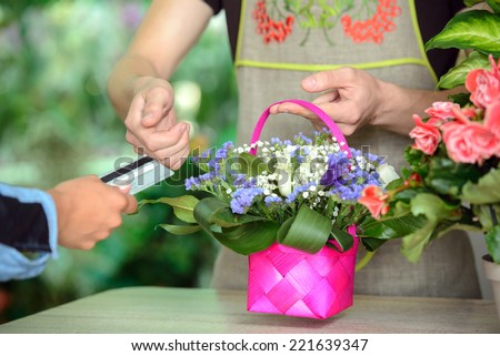 Young man working as florist giving credit card to customer after purchase. - stock photo