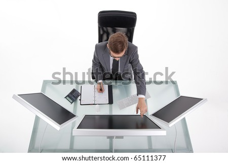 Young man working at his desk showing with the finger on his monitor - stock photo