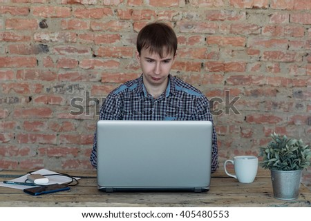 Young man working in office, sitting at desk, looking at laptop computer screen - stock photo