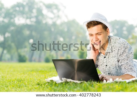 young man working in the park with a laptop - stock photo