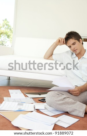 Young man working on his finances, sitting on the floor by the sofa. - stock photo