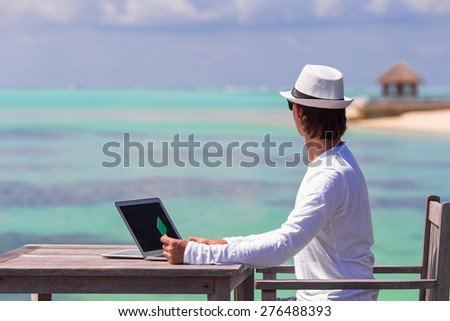 Young man working on laptop with credit card at tropical beach - stock photo