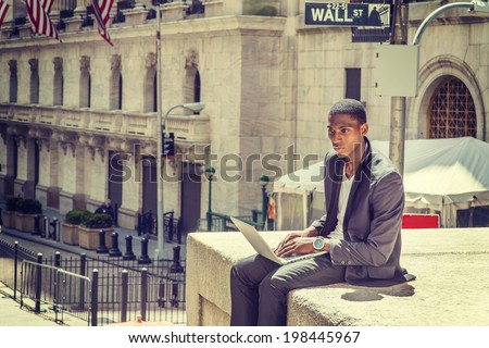 Young man working on street. A young black college student is sitting outside, typing on a laptop computer, looking down, thinking.  Wall Street sign in the background. - stock photo