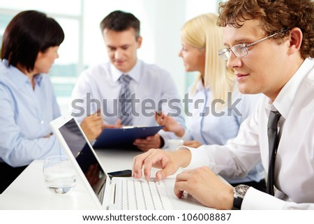 Young man working on the laptop, his colleagues holding a discussion in the background - stock photo