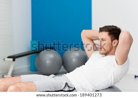 Young man working out at the gym doing pilates exercises balancing over the ball with his hands clasped behind his head toning his muscles and staring ahead with a serious expression, side view - stock photo