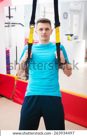 Young man working out with TRX in the gym. - stock photo