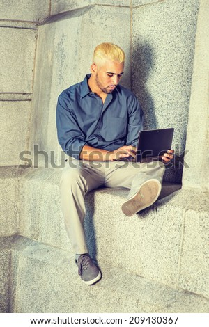 Young Man Working Outside. Wearing a blue shirt, gray pants, casual shoes, a young guy with beard, yellow hair is sitting by a concrete wall, looking down, working on a laptop computer. - stock photo