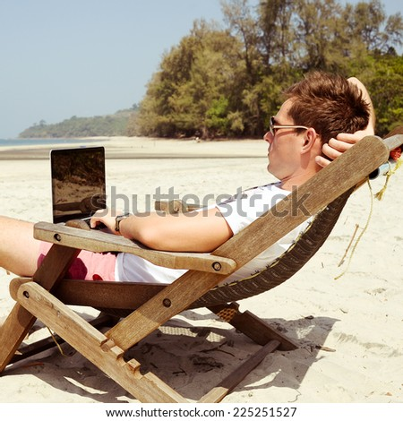 Young man working with laptop in a beach - stock photo