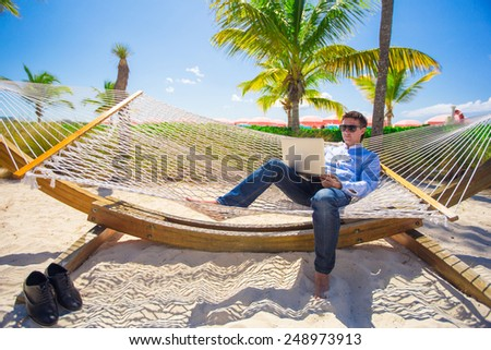 Young man working with laptop in hammock during beach vacation - stock photo