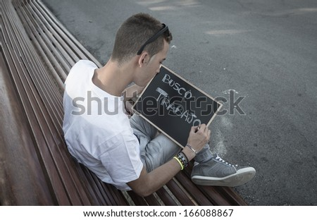 Young man writing I need job in spanish on a blackboard  - stock photo