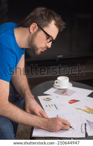 young man writing on paper in glasses. closeup image of hand writing using pen - stock photo