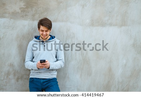 Young man writing sms standing by concrete wall. copy space - stock photo