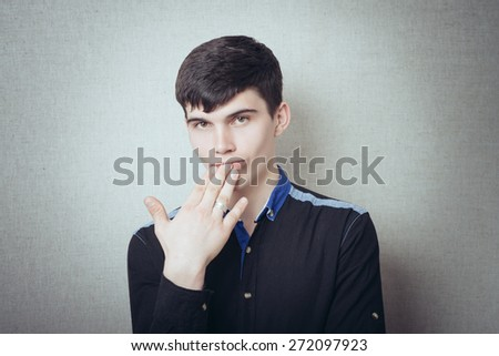 Young man yawns and covered his mouth with hand - stock photo