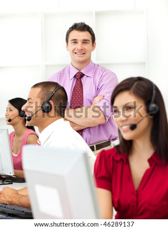 Young manager checking his employee's work in a call center - stock photo