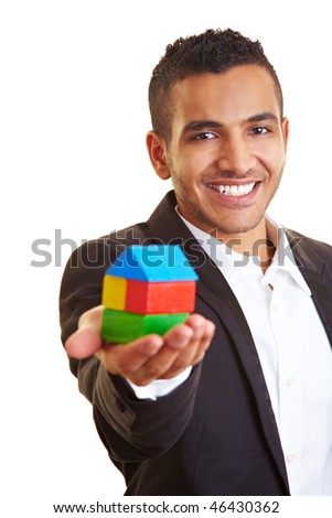 Young manager holding a house made of building bricks - stock photo