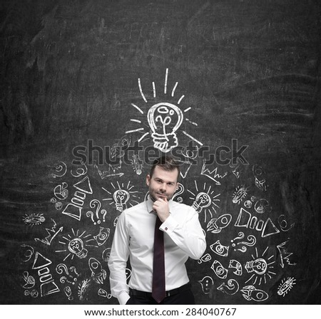 Young manager is thinking about new business ideas. Business icons and an yellow light bulb are drawn on the dark concrete wall. - stock photo