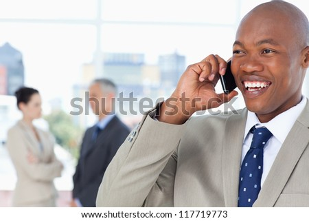 Young manager looking towards the side while laughing and talking on the phone - stock photo