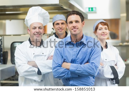 Young manager posing with some chefs in a kitchen  - stock photo
