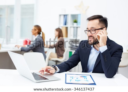 Young manager speaking on the phone and networking in office - stock photo