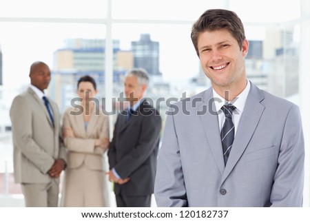 Young manager standing upright with his team behind him - stock photo