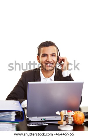 Young manager using a laptop with a headset - stock photo