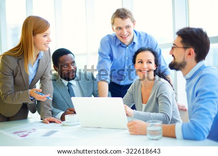 Young managers discussing plans at meeting - stock photo