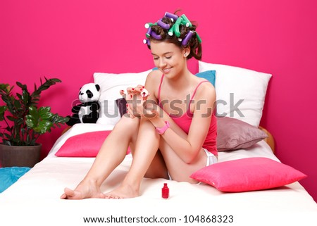 young manicurist applying red nail polish on her nails - stock photo