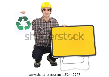 Young manual worker with recycle logo and blank road sign - stock photo